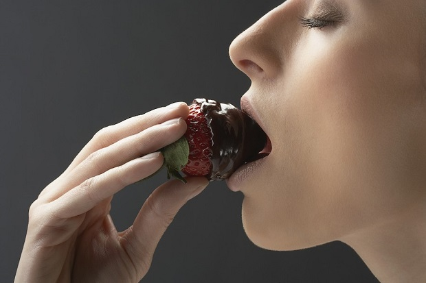 Woman bitting chocolate covered strawberry