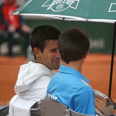 Novak Djokovic sonrie con un recoge pelotas a quien invita a sentarse a su lado mientras escampa