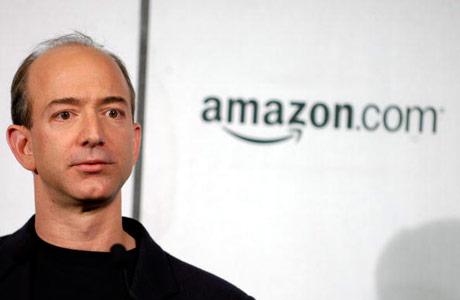 Jeff Bezzoz con logo de Amazon a sus espaldas