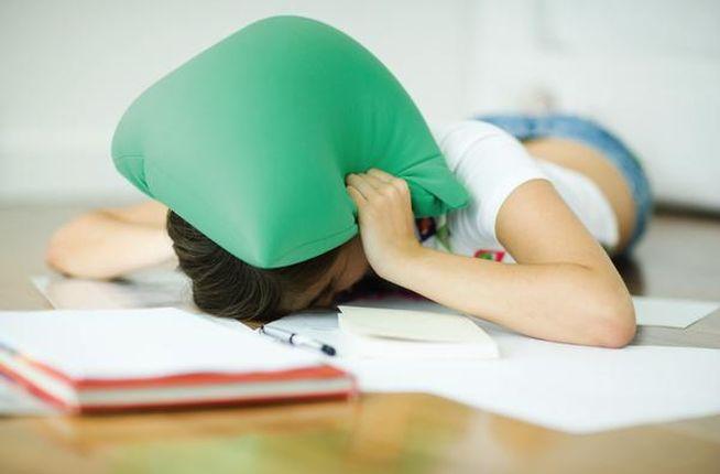 Chica estudia con cojín en la cabeza