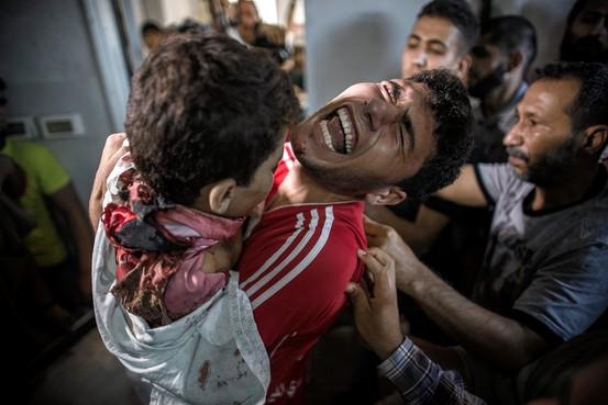 Padre llora mientras carga a su hijo muerto en Gaza