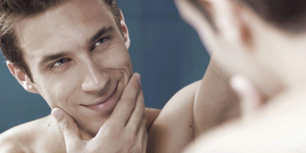 Hombre-narcisista-mirándose-al-espajo-mientras-se-acaricia-su-cara